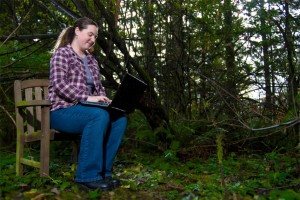 Kate with her laptop in the woods.