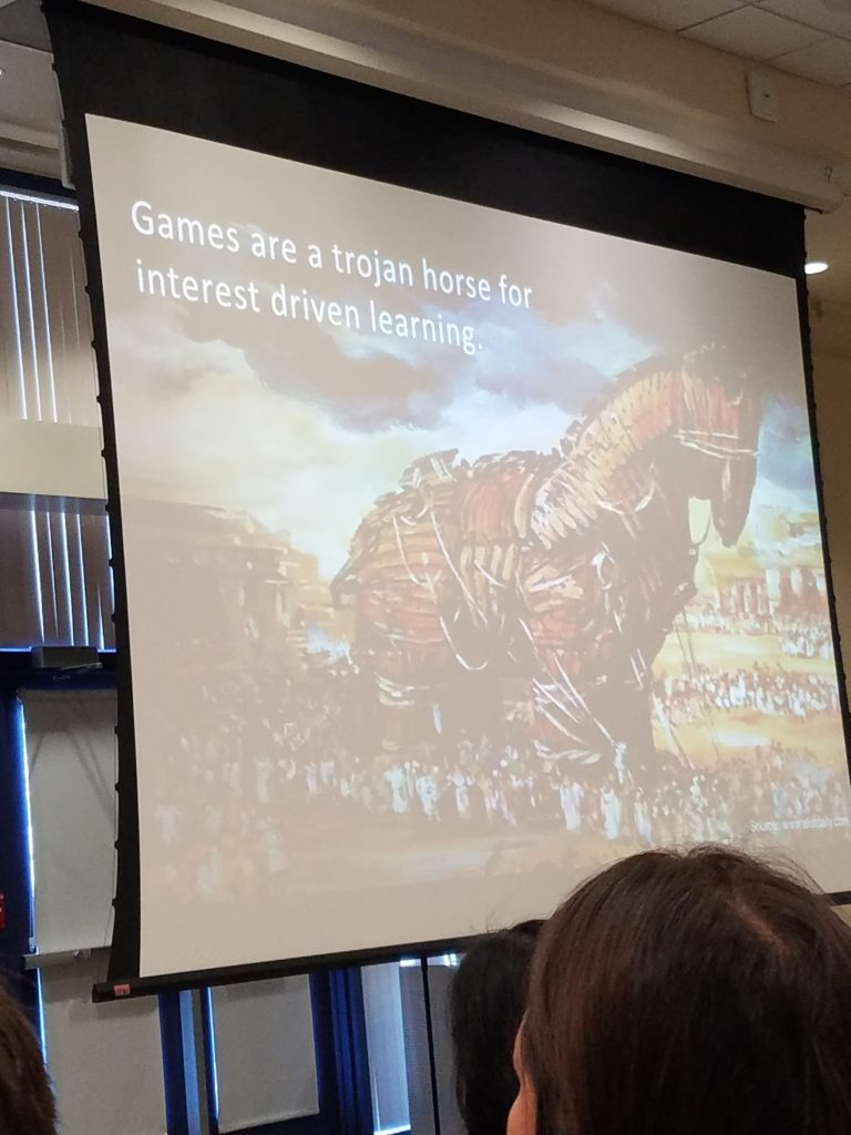 a photo of a slide of a trojan horse painted, with text reading games are a trojan horse for interest driven learning