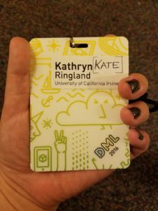 hand hold a DML conference badge, the text on the badge reads Kathryn Ringland Kate, University of California Irvine