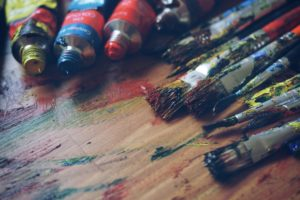 Paint tubes and paint brushes on a wooden table covered in different colored paints.