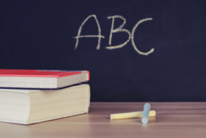 "A table with chalk and two books on it. In background is a chalkboard that read ""ABC""."