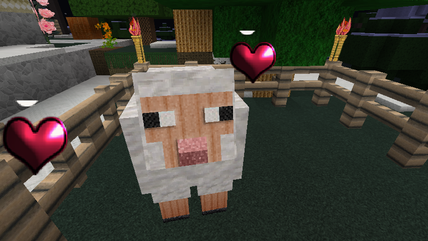 A white minecraft sheep in a pen with two red hearts floating by its head.